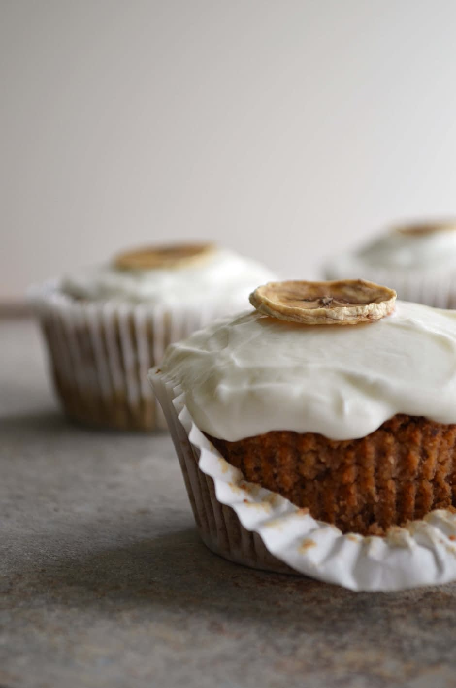 A photo of two healthy banana muffins with a Greek yogurt topping and dehydrated banana chips. Photo and recipe by That Healthy Kitchen