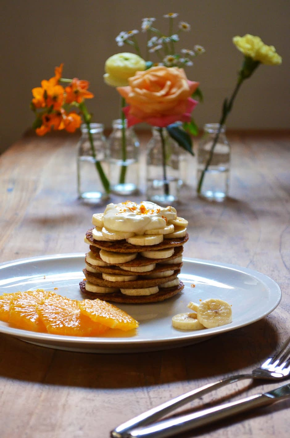 A stack of orange banana pancakes, topped with banana and orange slices. Recipe and photo by That Healthy Kitchen