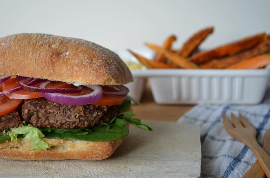 A photo of spicy black bean quinoa hamburger with sweet potato fries. Recipe by That Healthy Kitchen