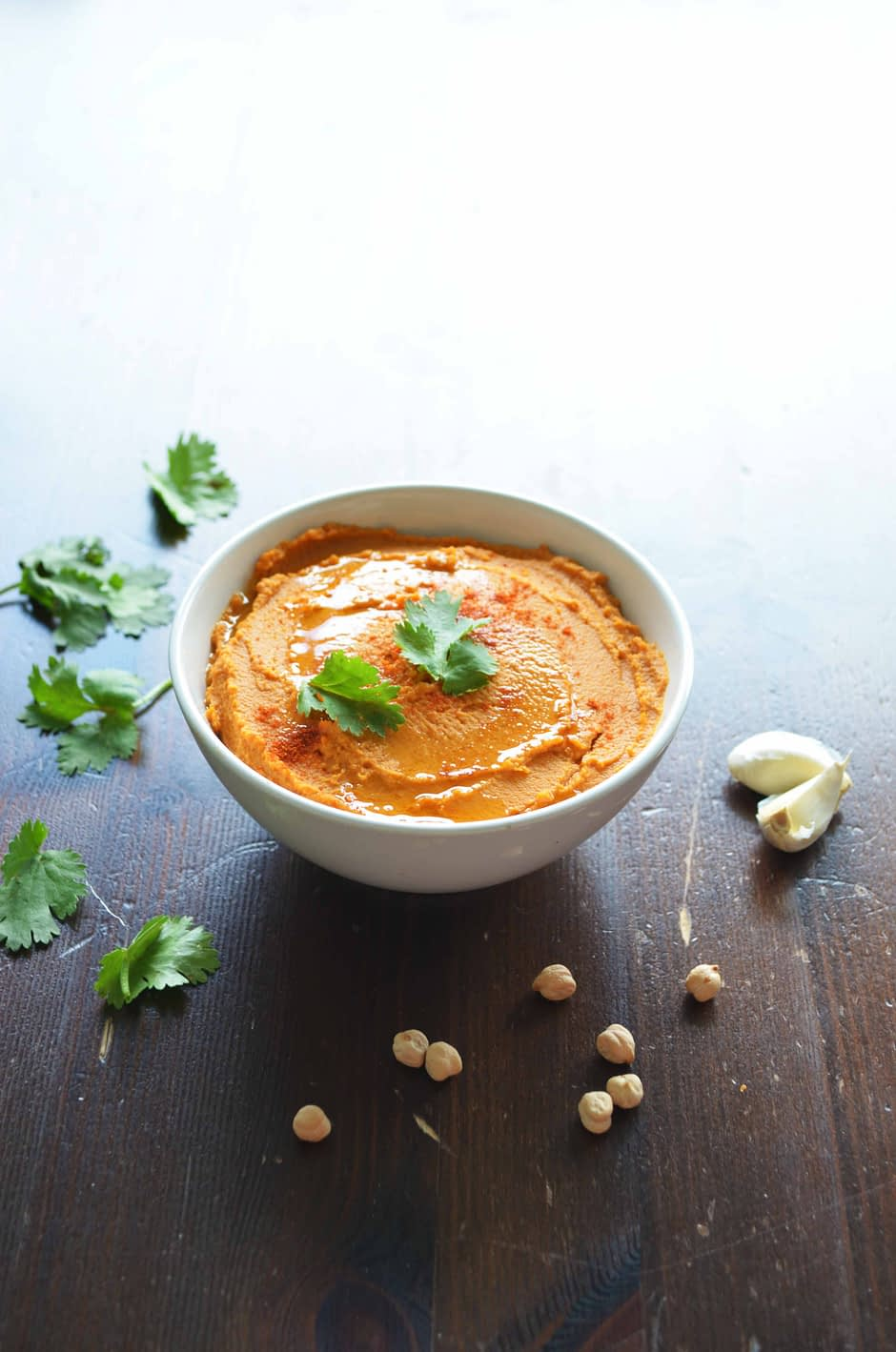 A white bowl filled with grilled red pepper (paprika) hummus, topped with cilantro. Recipe and photo by That Healthy Kitchen
