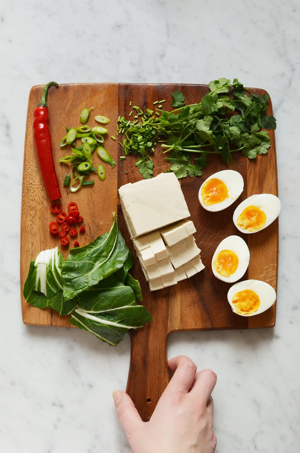 Recipe for spicy homemade ramen broth with all the toppings, including tofu, soft boiled eggs, fresh cilantro, red chili peppers, green onion, bok choy and buckwheat noodles. Gluten free!