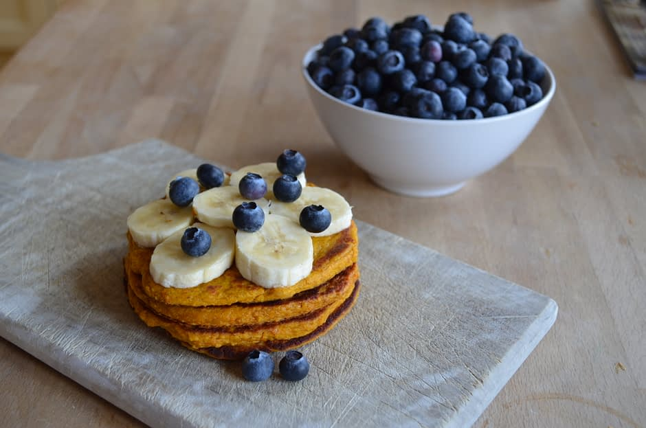 A photo of healthy pumpkin pancakes, topped with banana's and blueberries. The recipe is by That Healthy Kitchen