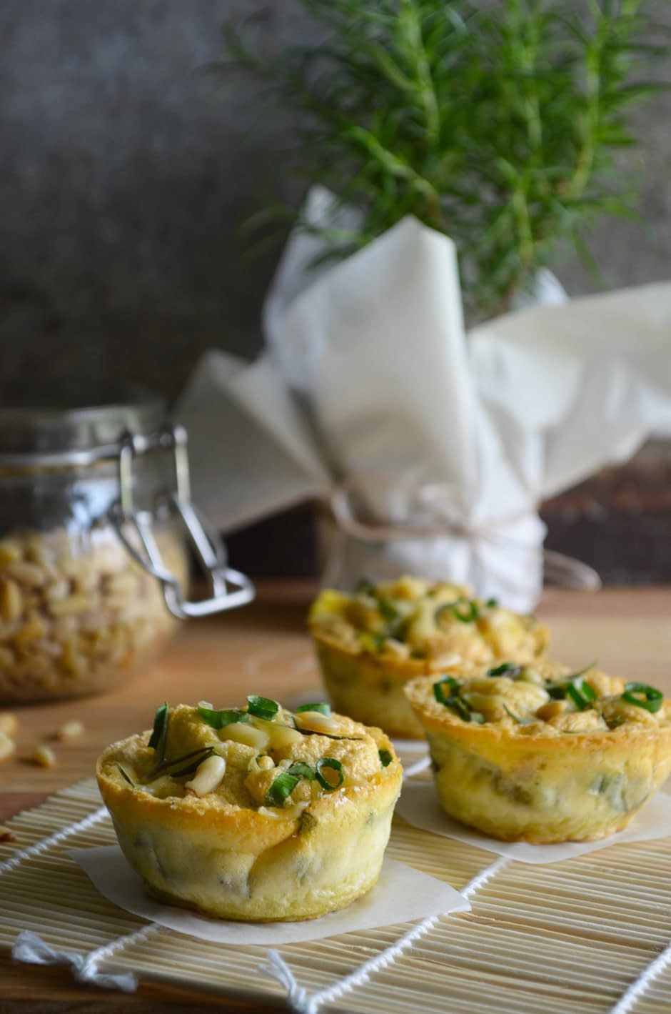 A photo of healthy egg muffins with rosemary, pine nuts and veggies. Recipe and photo by That Healthy Kitchen