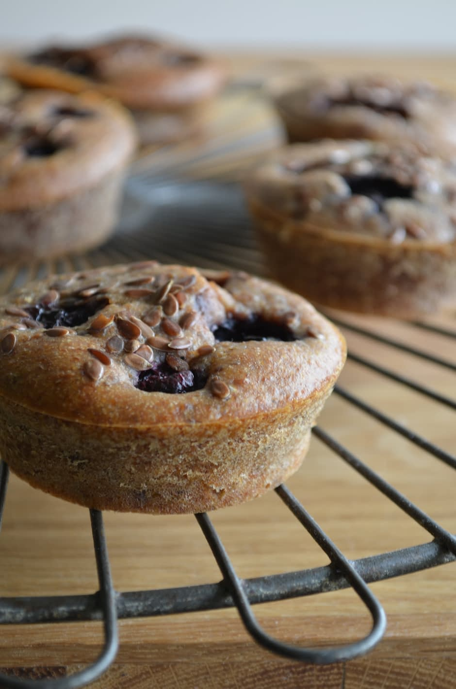 A photo of blueberry banana breakfast muffins, topped with flaxseed. Photo and recipe by That Healthy Kitchen