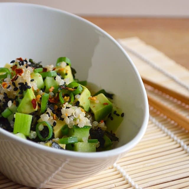 A bowl of sushi salad with quinoa, avocado, spring onion (green onion), black sesame seeds, nori and chili flakes. Photo and recipe by That Healthy Kitchen